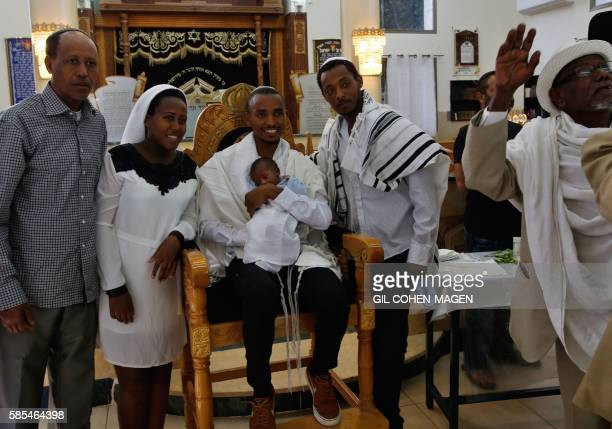 Marathon runner Ageze Guadie a 27yearold Israeli of Ethiopian origin holds his nephew during the circumcision of baby boy at a synagogue in Petah...
