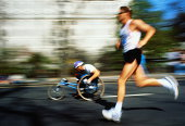Marathon runner and paraplegic contestant, blurred action
