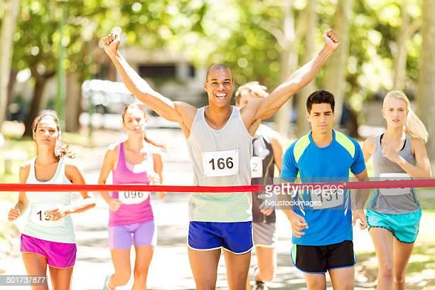 Marathon Runner With Arms Raised Crossing Finish Line