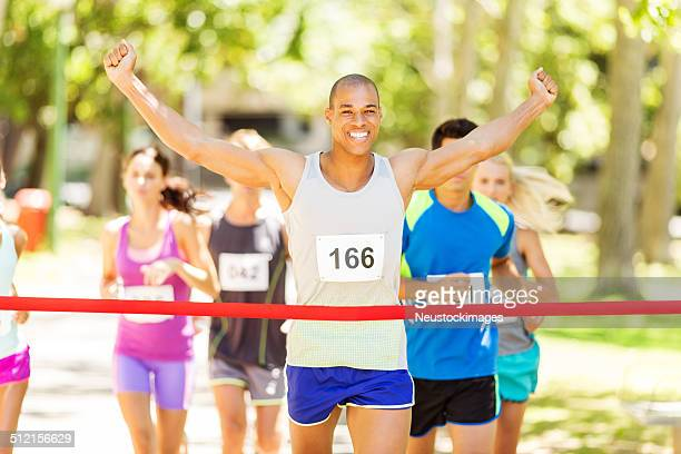 Marathon Runner With Arms Raised Crossing Finish Line
