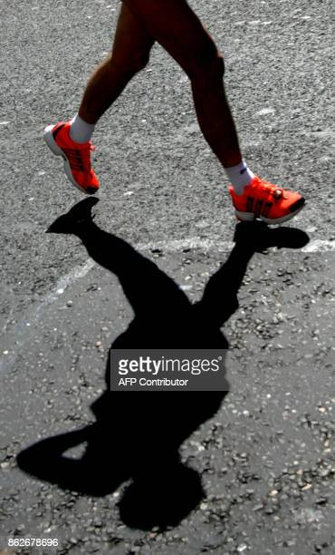 A marathon runner with brightly coloured trainer shoes casts a silhouette as he competes in the 25th annual London Marathon 17 April 2005 AFP...