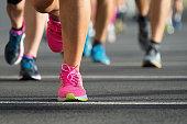 Marathon running race, people feet on city road