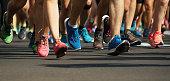 Marathon runners running on city road,detail on legs