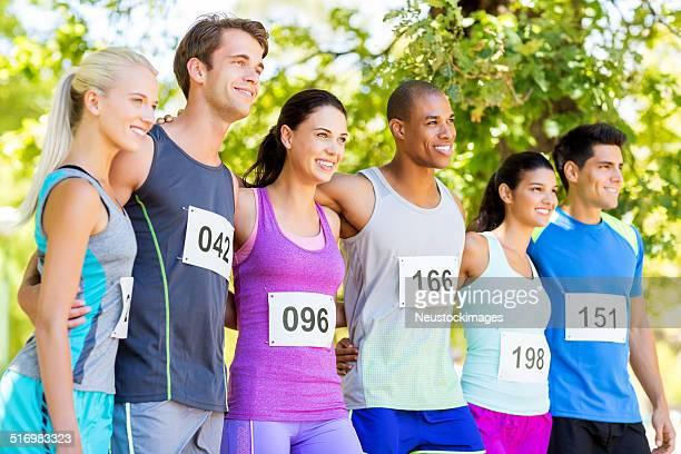 Marathon-Läufer stehend Arme um während Wegsehen