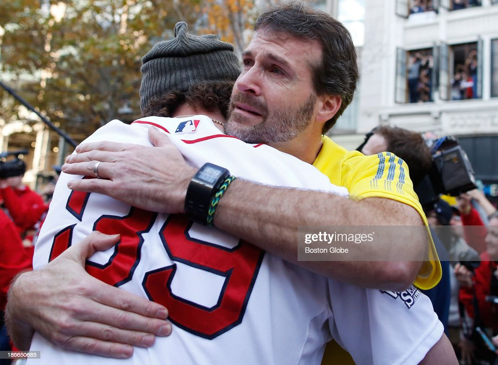 Marathon Sports Boston Store Manager Shane O'hara, right in yellow, embraces Boston Red Sox player Jarrod Saltalamacchia at the Boston Marathon finish line following a special ceremony in honor of the Boston Marathon bombing victims during the Rolling Rally duck boat parade to celebrate the Boston Red Sox's World Series victory on Saturday, Nov. 2, 2013.