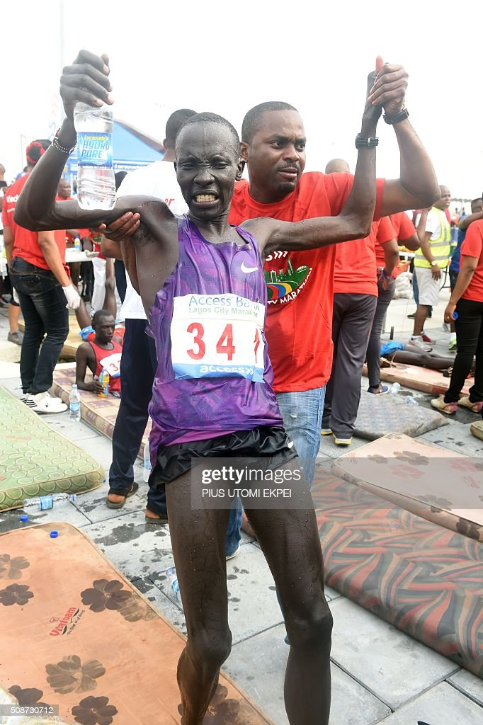 Marathon winner Kenyan Abraham Kipton is helped at the end of the first Lagos City Marathon, on February 6, 2016 in Lagos. / AFP / PIUS UTOMI EKPEI