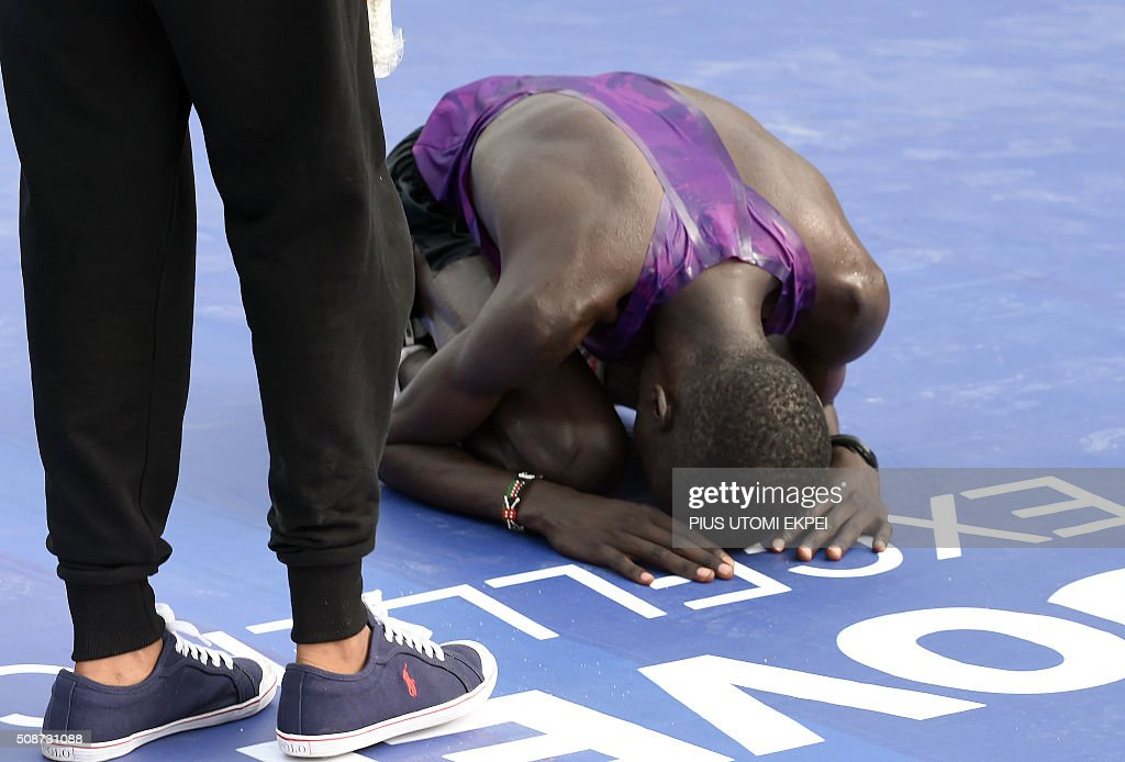 Marathon winner Kenyan Abraham Kipton prays after crossing the finishing line of the first Lagos City Marathon, on February 6, 2016 in Lagos. / AFP / PIUS UTOMI EKPEI