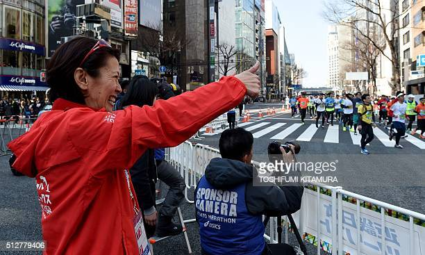 Marathon's Barcelona Olympics silver medalist and Atlanta Olympics bronze medalist Yuko Arimori of Japan gestures to competitors as they run through...
