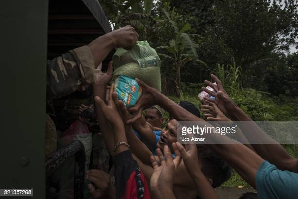 Marawi residents scramble to get food and supplies being handed out by a passing convoy of soldiers on July 21 2017 in Marawi southern Philippines...