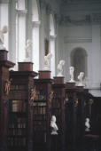 Marble busts of former members of Trinity College on display amongst bookshelves in the Wren Library Cambridge University circa 1975 The Wren library...
