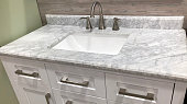 marble countertop on bathroom white cabinet with white rectangular under mount sink and chrome faucet