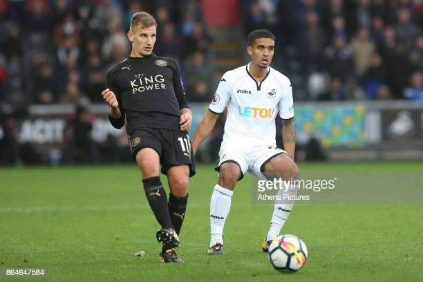 Marc Albrighton of Leicester City is marked by Kyle Naughton of Swansea City during the Premier League match between Swansea City and Leicester City...