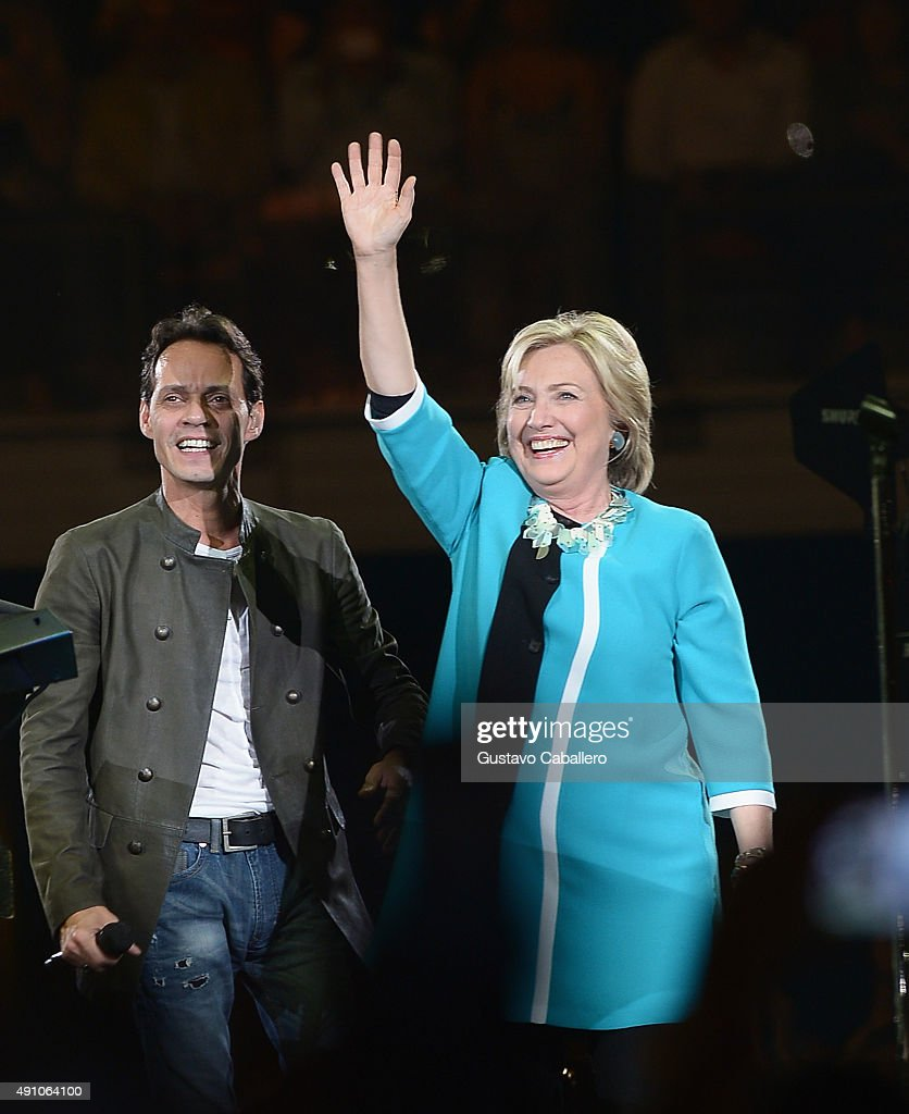 Marc Anthony and Hillary Clinton speak onstage at the Marc Anthony concert at American Airlines Arena on October 2 2015 in Miami Florida