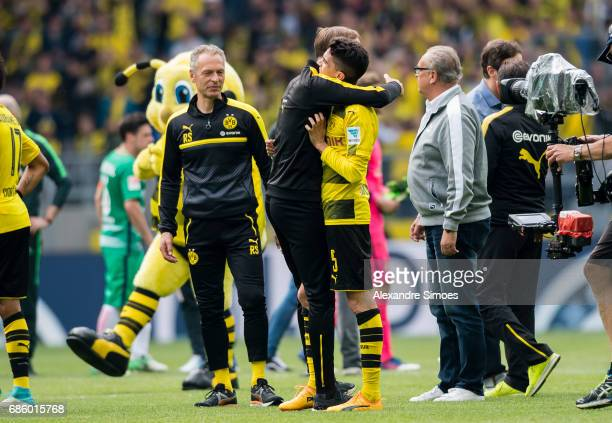Marc Bartra and his head coach Thomas Tuchel of Borussia Dortmund celebrate together after the final whistle during the Bundesliga match between...