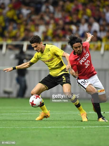 Marc Bartra of Borussia Dortmund and Shinzo Koroki of Urawa Red Diamonds compete for the ball during the preseason friendly match between Urawa Red...