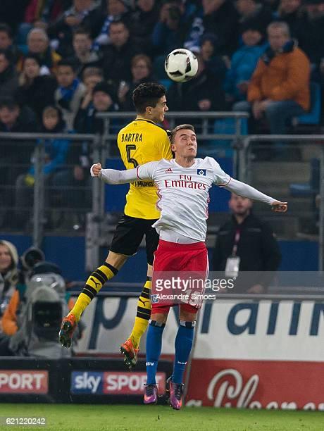 Marc Bartra of Borussia Dortmund challenges Waldschmidt of Hamburger SV in an aerial duel during the Bundesliga match between Hamburger SV and...
