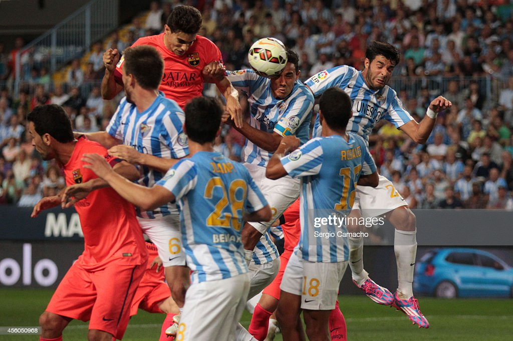Marc Bartra of FC Barcelona has a head shot on goal under pressure from Weligton Robson of Malaga CF during the La Liga match between Malaga CF and...