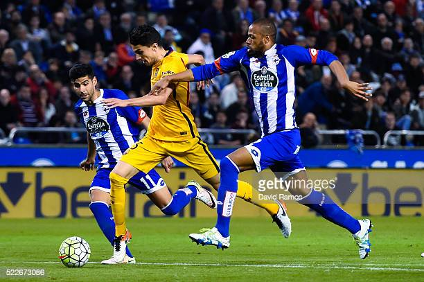 Marc Bartra of FC Barcelona vies for the ball with Juanfran Moreno and Sidnei Rechel da Silva of RC Deportivo La Coruna to scores his team's seventh...