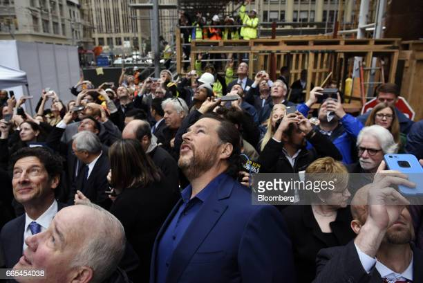 Marc Benioff chairman and chief executive officer of Salesforcecom Inc center watches as the final steel beam is hoisted up during a topping off...