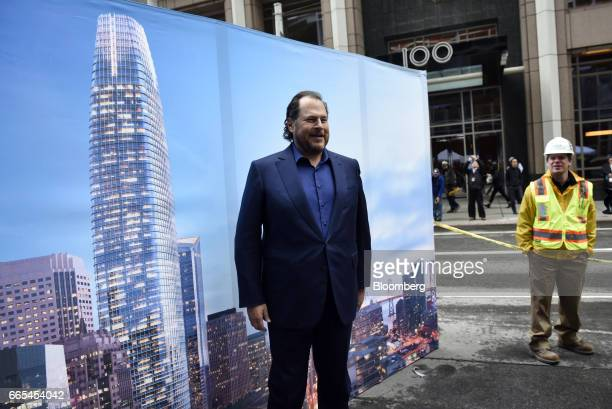 Marc Benioff chairman and chief executive officer of Salesforcecom Inc stands in front of a poster during a topping off ceremony for the Salesforce...
