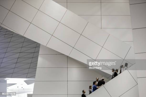 Marc Benioff chairman and chief executive officer of Salesforcecom Inc fourth from left and other attendees travel up an escalator at the World...