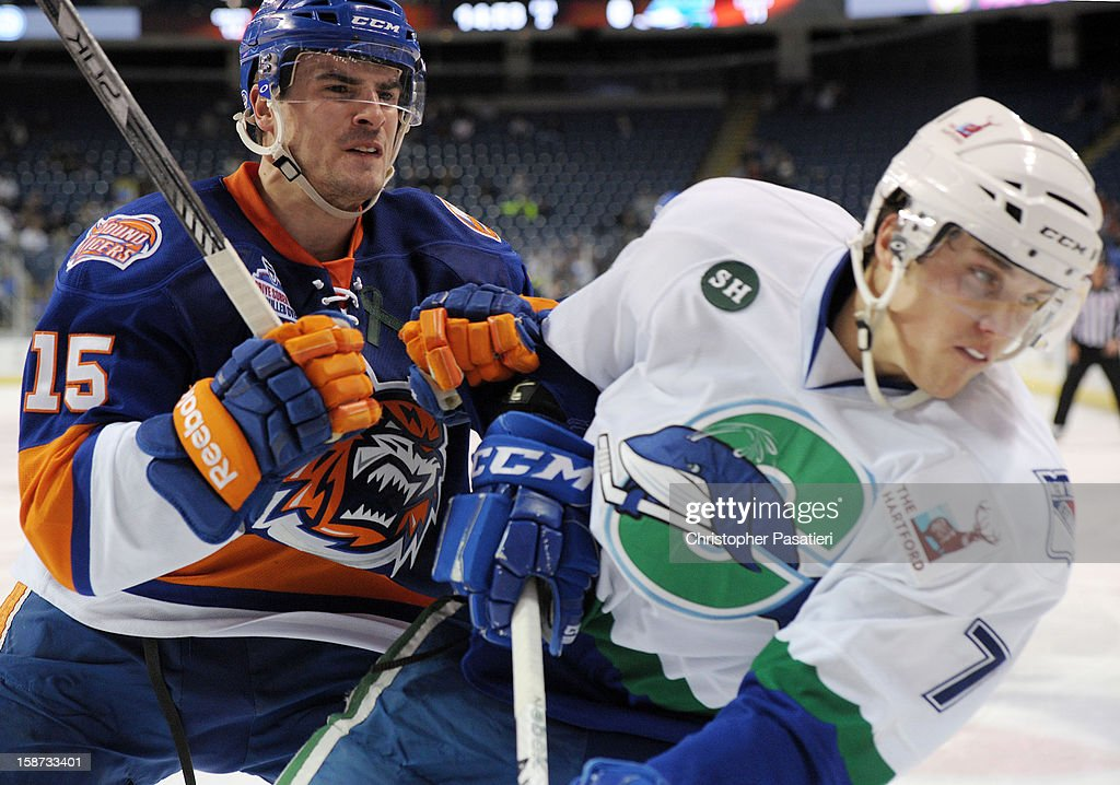 Marc Cantin #15 of the Bridgeport Sound Tigers checks Kyle Jean #7 of the Connecticut Whale during an American Hockey League game on December 26, 2012 at the Webster Bank Arena at Harbor Yard in Bridgeport, Connecticut.