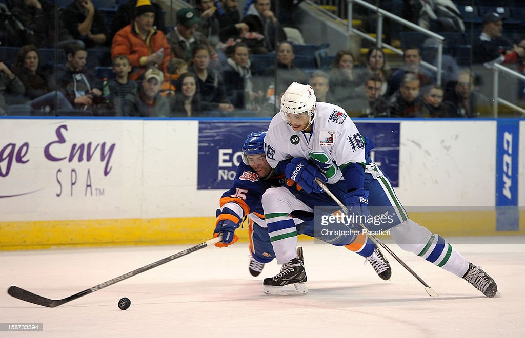 Marc Cantin #15 of the Bridgeport Sound Tigers reaches for the puck against Tommy Grant #16 of the Connecticut Whale during an American Hockey League on December 26, 2012 at the Webster Bank Arena at Harbor Yard in Bridgeport, Connecticut.