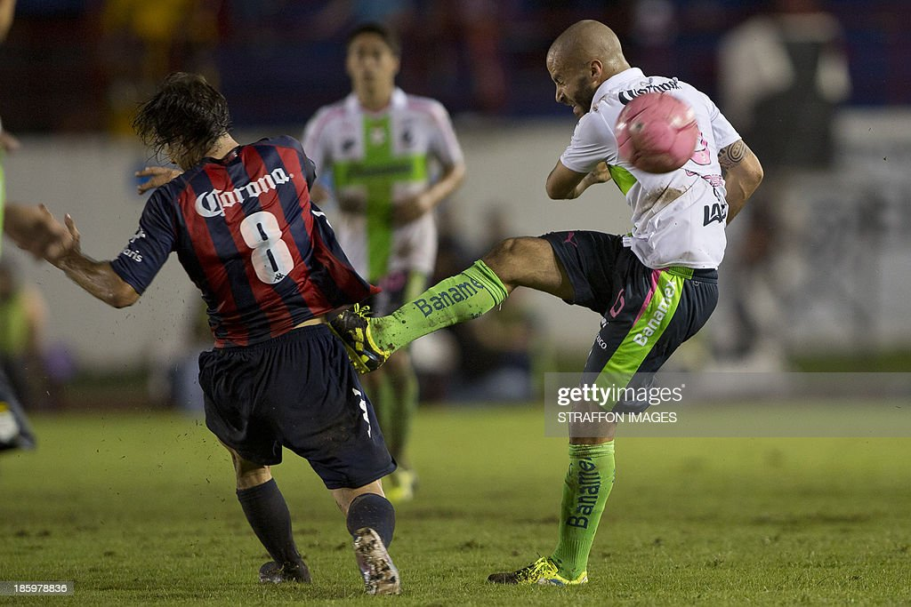 Marc Crosas of Santos fights for the ball with Martin Galmarini of Atlante during a match between Atlante and Santos Laguna as part of the Apertura 2013 Liga MX at Olympic Stadium Andres Quintana Roo on October 26, 2013 in Cancun, Mexico.