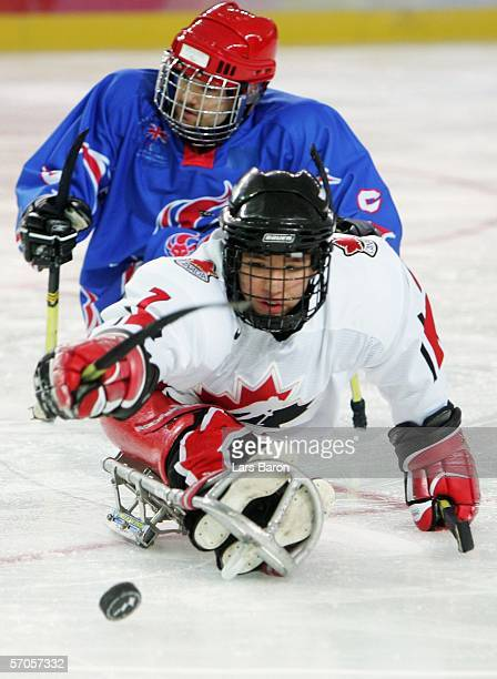 Marc Dorion of Canada reaches for the puck with Karl Nicholson of Great Britain during a sledge hockey preliminary round Group A match between Canada...
