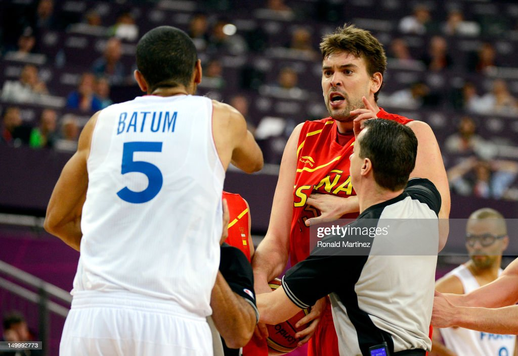 <a gi-track='captionPersonalityLinkClicked' href=/galleries/search?phrase=Marc+Gasol&family=editorial&specificpeople=661205 ng-click='$event.stopPropagation()'>Marc Gasol</a> #13 of Spain is held back by a referee as he runs towards <a gi-track='captionPersonalityLinkClicked' href=/galleries/search?phrase=Nicolas+Batum&family=editorial&specificpeople=3746275 ng-click='$event.stopPropagation()'>Nicolas Batum</a> #5 of France after Batum fouled Juan-Carlos Navarro #7 late in the fourth quarter during the Men's Basketball quaterfinal game on Day 12 of the London 2012 Olympic Games at North Greenwich Arena on August 8, 2012 in London, England.