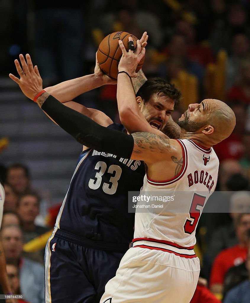 <a gi-track='captionPersonalityLinkClicked' href=/galleries/search?phrase=Marc+Gasol&family=editorial&specificpeople=661205 ng-click='$event.stopPropagation()'>Marc Gasol</a> #33 of the Memphis Grizzles is pressured by <a gi-track='captionPersonalityLinkClicked' href=/galleries/search?phrase=Carlos+Boozer&family=editorial&specificpeople=201638 ng-click='$event.stopPropagation()'>Carlos Boozer</a> #5 of the Chicxago Bulls at the United Center on January 19, 2013 in Chicago, Illinois. The Grizzlies defeated the Bulls 85-82 in overtime.