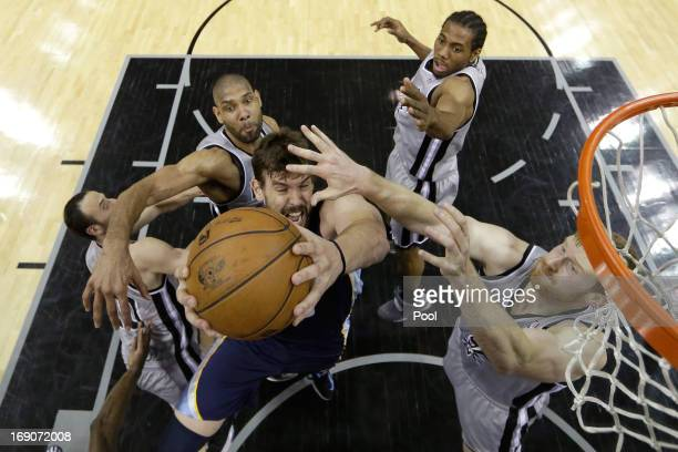 Marc Gasol of the Memphis Grizzlies drives for a shot attempt against Tim Duncan and Matt Bonner of the San Antonio Spurs during Game One of the...