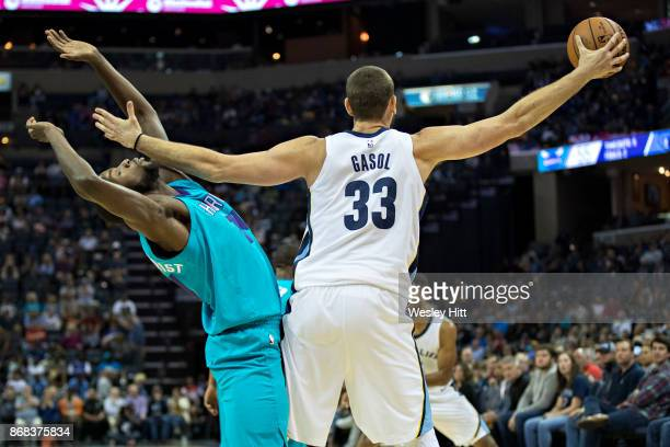 Marc Gasol of the Memphis Grizzlies reaches for a pass and fouls Michael KiddGilchrist of the Charlotte Hornets at the FedEx Forum on October 30 2017...