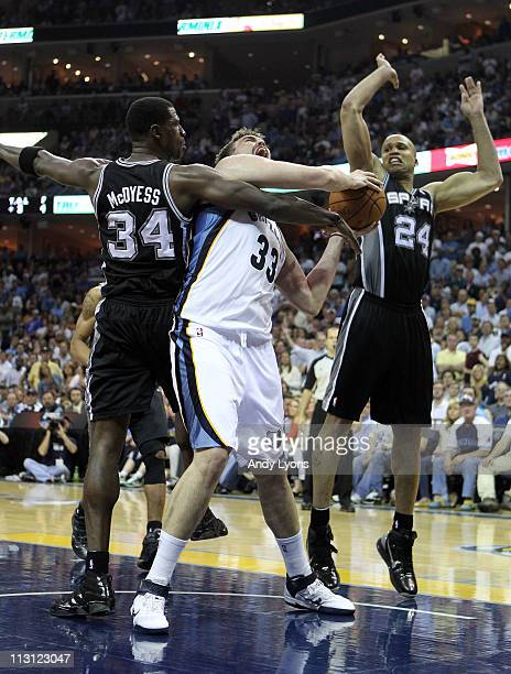 Marc Gasol of the Memphis Grizzlies shoots the ball while defended by Antonio McDyess and Richard Jefferson of the San Antonio Spurs in Game three of...