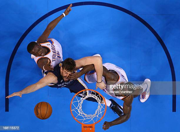 Marc Gasol of the Memphis Grizzlies takes a shot against Reggie Jackson and Kendrick Perkins of the Oklahoma City Thunder during Game One of the...