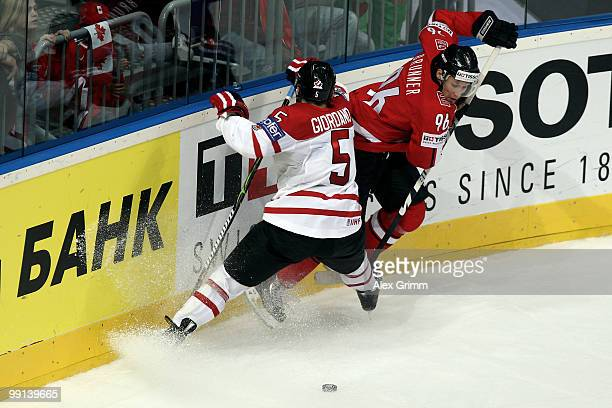 Marc Giordano of Canada is challenged by Damien Brunner of Switzerland during the IIHF World Championship group C match between Canada and...
