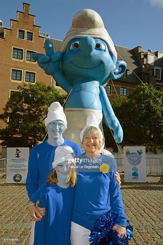 Marc Guerin, Nina Guerin Culliford and Veronique Culliford, the daughter of cartoonist Peyo, the creator of The Smurfs, pose by a giant Smurf character during Global Smurfs Day celebrations on June 22, 2013 in Brussels, Belgium.