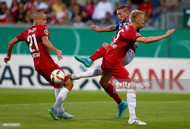 Marc Heider of Holstein Kiel is challenged by dam Hlousek and Timo Baumgartl of VfB Stuttgart during the DFB Cup First Round match between Holstein...