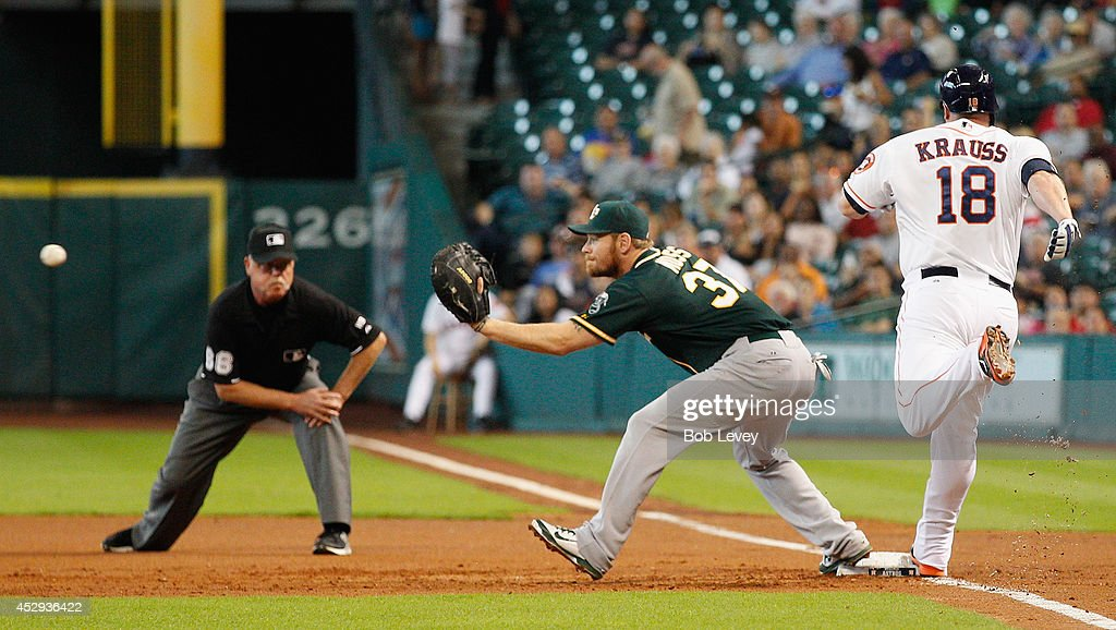 Marc Krauss #18 of the Houston Astros beats the throw as <a gi-track='captionPersonalityLinkClicked' href=/galleries/search?phrase=Brandon+Moss&family=editorial&specificpeople=702783 ng-click='$event.stopPropagation()'>Brandon Moss</a> #37 of the Oakland Athletics awaits the ball in the first inning at Minute Maid Park on July 30, 2014 in Houston, Texas.