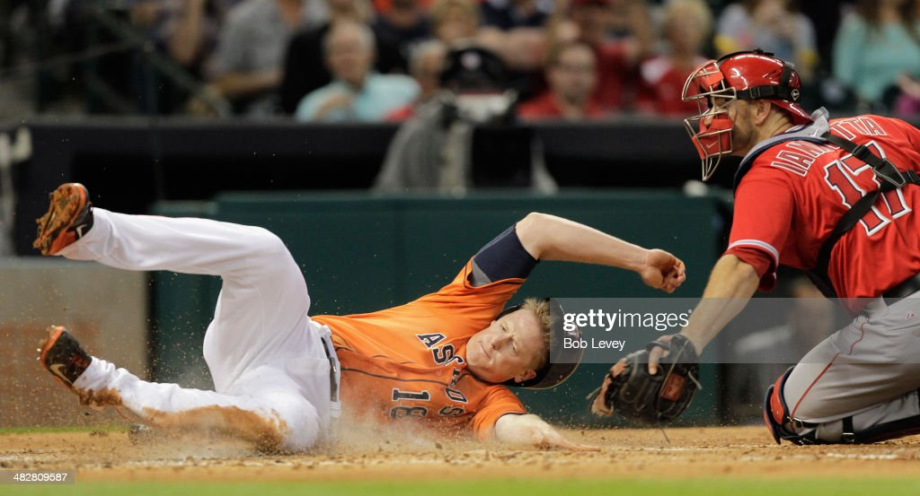 Marc Krauss #18 of the Houston Astros is tagged out by catcher Chris Iannetta #17 of the Los Angeles Angels of Anaheim in the second inning at Minute Maid Park on April 4, 2014 in Houston, Texas.