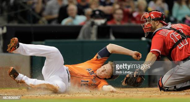 Marc Krauss of the Houston Astros is tagged out by catcher Chris Iannetta of the Los Angeles Angels of Anaheim in the second inning at Minute Maid...