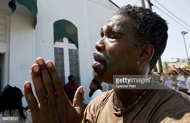 Marc Leggett prays while attending a Sunday service outside of the Lighthouse Apostolic Church which was damaged by Hurricane Katrina September 11...