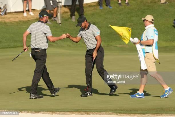 Marc Leishman and Jason Day of Australia and the International Team fistbump on a green during the second round of the Presidents Cup at Liberty...