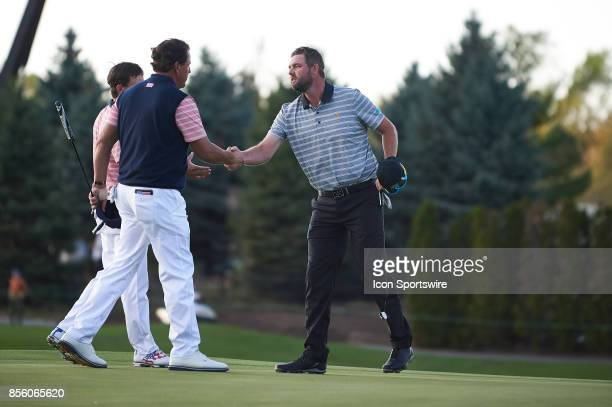 Marc Leishman of Australia and of the International Team shake hands with Phil Mickelson and Kevin Kisner of the American Team on the 18th green...