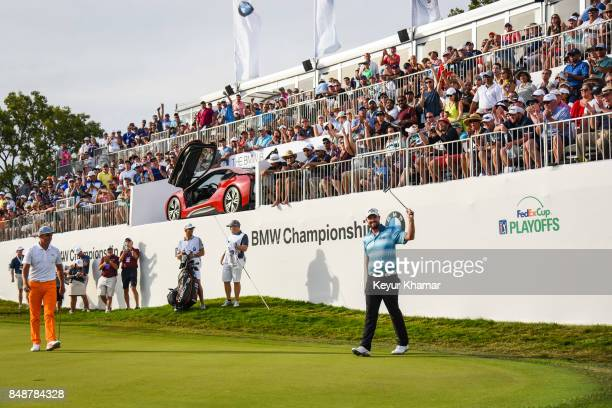 Marc Leishman of Australia celebrates and raises his putter to fans after making a birdie putt on the 18th hole green during the final round of the...