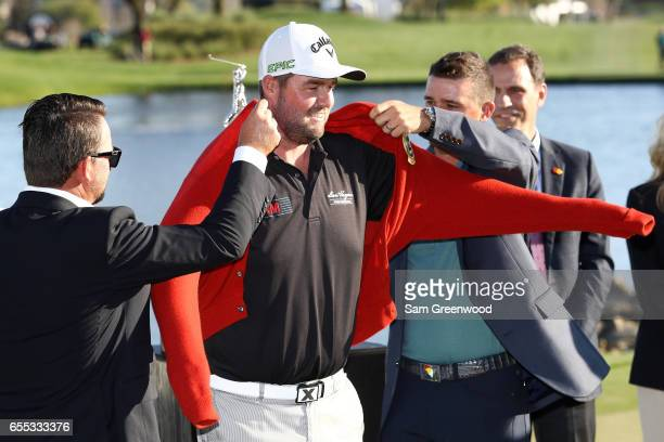 Marc Leishman of Australia celebrates with the Arnie's Army cardigan on the 18th green after winning the Arnold Palmer Invitational Presented By...
