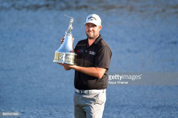 Marc Leishman of Australia holds the winner's trophy after his onestroke victory on the 18th hole green during the final round of the Arnold Palmer...