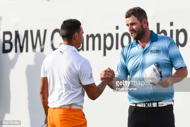 Marc Leishman of Australia shakes hands with Rickie Fowler on the 18th hole green following his five stroke victory in the final round of the BMW...