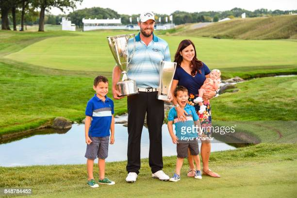 Marc Leishman of Australia smiles while holding the Western Golf Association Open JK Wadley Championship Cup and tournament trophy with his wife...