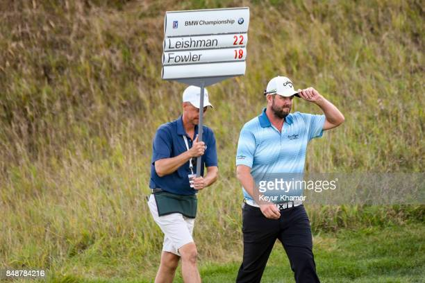 Marc Leishman of Australia tips his cap to fans as he walks to the 18th hole green with a volunteer standard bearer during the final round of the BMW...